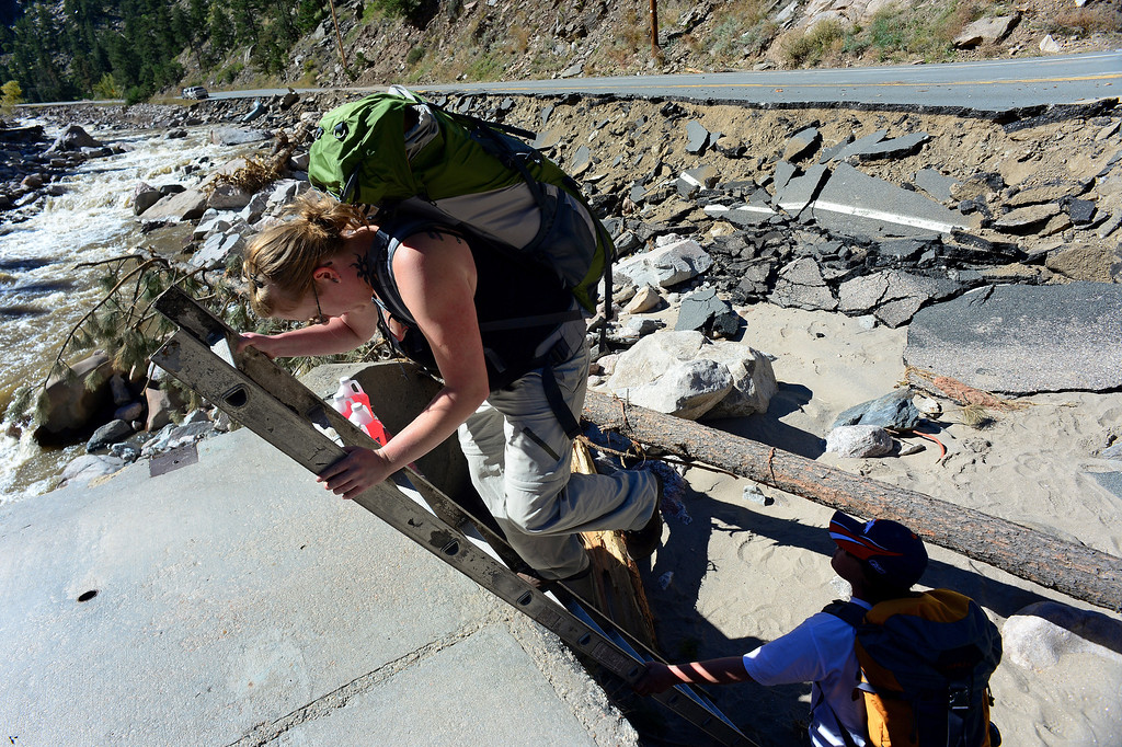. DRAKE, CO - OCTOBER 1:  Amber Okuley, descends a ladder to get off of what is left of a bridge into the house of her friend and homeowner Heather McGurn, right.  The two were bringing out left  out as many personal items from McGurn\'s house in Drake, Co. October 1, 2013, before closing it for the winter.  It was the first time McGurn and her husband Richard were allowed back into Drake to even see if their home was still standing.  The house was there but the entire property has been destroyed by the flood.  (Photo By Helen H. Richardson/ The Denver Post)