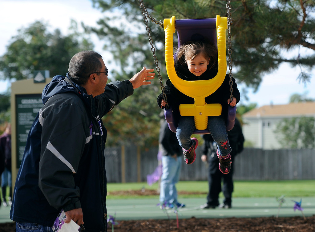 . WESTMINSTER, CO - Oct. 5: Destiny Torres, 3, gets a ride in a new bright purple swing with a little help from her grandfather, David Amaro. Amaro was one of the volunteers that helped put the new park together. A year to the day since Jessica Ridgeway went missing, a dedication ceremony takes place in her memory at the Jessica Ridgeway Memorial Park. Jessica\'s family and hundreds of others gather at the newly renovated park (much of the playground equipment made in Jessica\'s favorite color purple) that came together through the dedication of volunteers throughout the community. (Photo By Kathryn Scott Osler/The Denver Post)