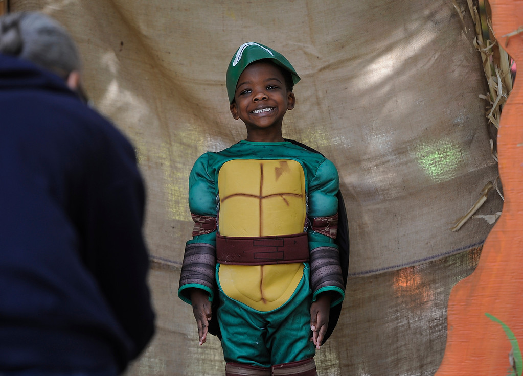 . DENVER, CO - Oct. 25: Families gather at the giant pumpkin to get photos of their trick-or-treaters. Teenage Mutant Ninja Turtle Cairo Murphy, 3, gives grandma Michele James-Penick the perfect pose. The Children\'s Museum of Denver hosts its annual Trick or Treat Street with trick-or-treating from the various Treat Houses, train rides on Vern\'s Mini Train, Monster Carnival, arts and crafts, and more. The event runs both Saturday and Sunday from 10 a.m to 7 p.m. (Photo By Kathryn Scott Osler/The Denver Post)