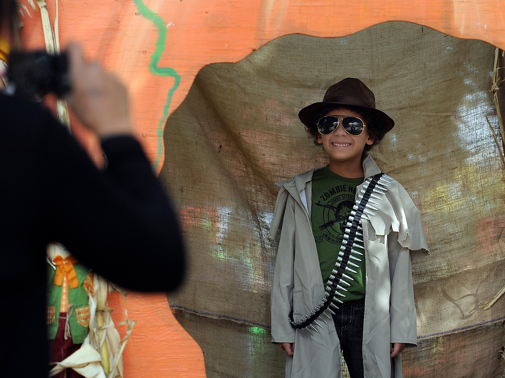 . DENVER, CO - Oct. 25: Families gather at the giant pumpkin to get photos of their trick-or-treaters. Zombie hunter Roland Isaiah Thornton, 7, puts on his shades to complete the costume for grandma Linda Thornton. The Children\'s Museum of Denver hosts its annual Trick or Treat Street with trick-or-treating from the various Treat Houses, train rides on Vern\'s Mini Train, Monster Carnival, arts and crafts, and more. The event runs both Saturday and Sunday from 10 a.m to 7 p.m. (Photo By Kathryn Scott Osler/The Denver Post)
