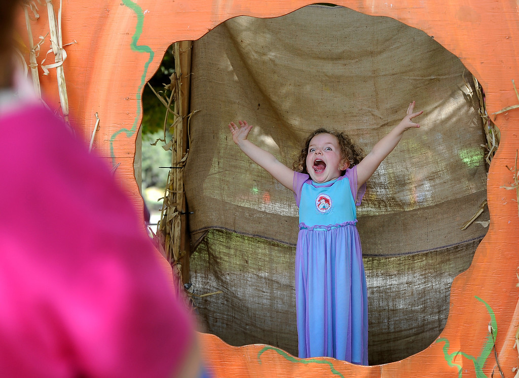 . DENVER, CO - Oct. 25: Families gather at the giant pumpkin to get photos of their trick-or-treaters. Mom Kristen Hickey grabs a moment of daughter Claire, 3, who is Disney\'s Ariel. The Children\'s Museum of Denver hosts its annual Trick or Treat Street with trick-or-treating from the various Treat Houses, train rides on Vern\'s Mini Train, Monster Carnival, arts and crafts, and more. The event runs both Saturday and Sunday from 10 a.m to 7 p.m. (Photo By Kathryn Scott Osler/The Denver Post)