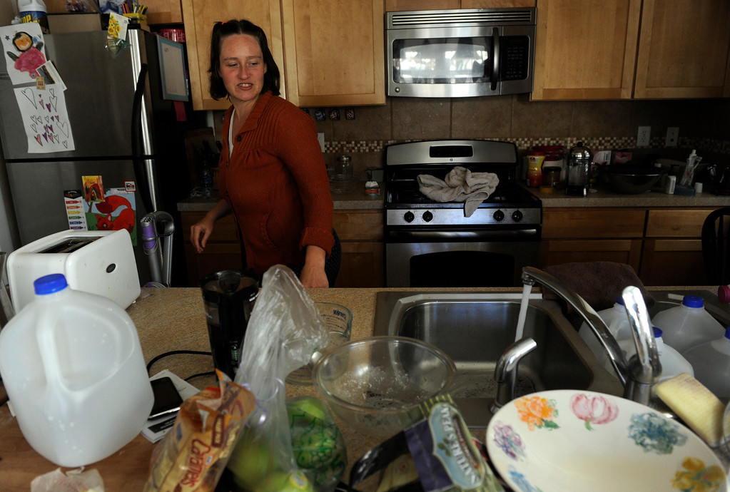 . LYONS, CO - Oct. 26: Erica Joy Besen watches as water pours out of her faucet for the first time in over a month. About 1,000 residents from the city of Lyons are expected to return home this weekend as water, sewage and gas are restored in homes. The town has been without utilities since mid-September after the St. Vrain River flooded homes and businesses and damaged the town\'s electric, water and sewer lines forcing community-wide evacuations. Crews have shattered original predicted timelines of at least three months for when utilities would be restored. (Photo By Kathryn Scott Osler/The Denver Post)
