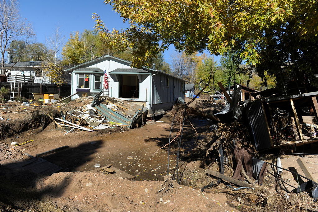 . LYONS, CO - Oct. 26: Even as thousands of residents have utilities restored to their homes, much of Lyons, especially on the south side of town,  is still devastated and working to recover and some homes remain abandoned. About 1,000 residents from the city of Lyons are expected to return home this weekend as water, sewage and gas are restored in homes. The town has been without utilities since mid-September after the St. Vrain River flooded homes and businesses and damaged the town\'s electric, water and sewer lines forcing community-wide evacuations. Crews have shattered original predicted timelines of at least three months for when utilities would be restored. (Photo By Kathryn Scott Osler/The Denver Post)