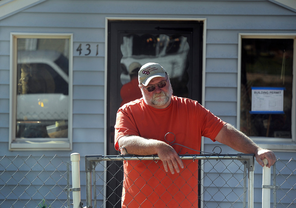 . LYONS, CO - Oct. 26: Dennis Smith watches and waits patiently in front of his home as Xcel Energy workers pull up in their trucks to restore gas to his and other area homes. About 1,000 residents from the city of Lyons are expected to return home this weekend as water, sewage and gas are restored in homes. The town has been without utilities since mid-September after the St. Vrain River flooded homes and businesses and damaged the town\'s electric, water and sewer lines forcing community-wide evacuations. Crews have shattered original predicted timelines of at least three months for when utilities would be restored. (Photo By Kathryn Scott Osler/The Denver Post)