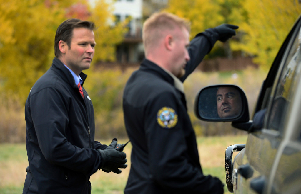 . Colorado Parks and Wildlife officer Justin Olson, center, talks with his partner Matt Martinez, in window about the growing number of curious onlookers coming out to view the bull moose in the Stonegate subdivision in in Parker on Monday, October 28, 2013.     (Photo By Helen H. Richardson/ The Denver Post)