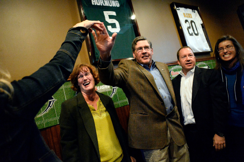. CASTLE ROCK, CO - NOVEMBER 05: Douglas County School Board Judith Reynolds, Jim Geddes high fives a supporter, Doug Benevento and Meghann Silverthorn celebrate at the Fowl Line November 5, 2013 on election night. (Photo by John Leyba/The Denver Post)