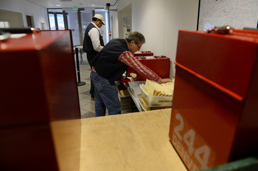 . DENVER, CO - NOVEMBER 05: Denver Election judges, Jesse Miller, left, and Ed Moss, left, collect ballots at a receiving station at Denver Election headquarters Tuesday, November 05, 2013. (Photo By Andy Cross/The Denver Post)