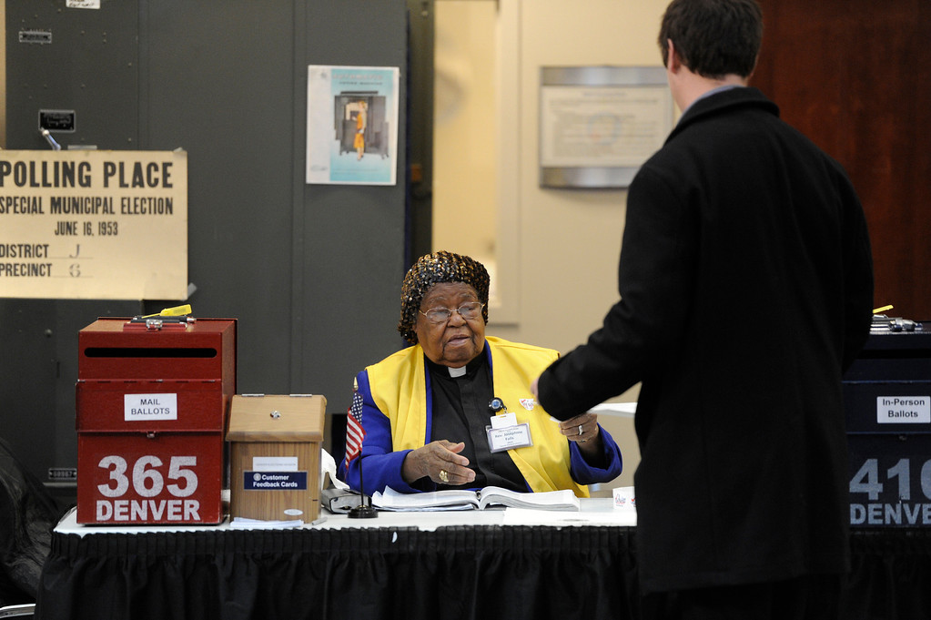 . DENVER, CO - NOVEMBER 05:  Denver Election support judge,  Rev. Josephine Falls, left, looks over a voter\'s information at the Denver Election headquarters Tuesday morning, November 05, 2013. (Photo By Andy Cross/The Denver Post)