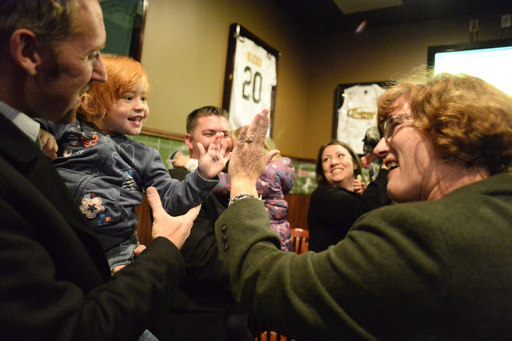 . CASTLE ROCK, CO - NOVEMBER 05: Douglas County School Board Judith Reynolds gets a high five from Hannah Hawley 3 years old as they celebrate at the Fowl Line November 5, 2013 on election night. (Photo by John Leyba/The Denver Post)