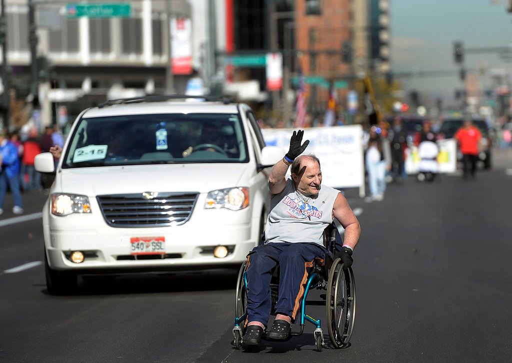 . DENVER, CO - NOV. 9: Nicholas Patrick, representing the Mountain States Chapter of Paralyzed Veterans of America, waves to the crowds as he makes his way down Broadway during the parade. The largest annual Denver Veteran\'s Day Celebration takes place starting with a 5k run and continuing with a parade and remembrance ceremony downtown next to Civic Center Park, and finishing on the Auraria campus with activities and fireworks. (Photo By Kathryn Scott Osler/The Denver Post)
