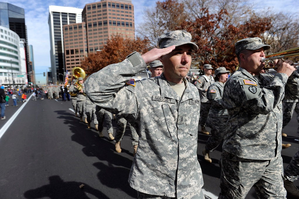. DENVER, CO - NOV. 9: A guardsman salutes as he walks next to members of the 101st Army Band for the Colorado National Guard from Buckley Air Force Base in Aurora head down Broadway during the parade. The largest annual Denver Veteran\'s Day Celebration takes place starting with a 5k run and continuing with a parade and remembrance ceremony downtown next to Civic Center Park, and finishing on the Auraria campus with activities and fireworks. (Photo By Kathryn Scott Osler/The Denver Post)