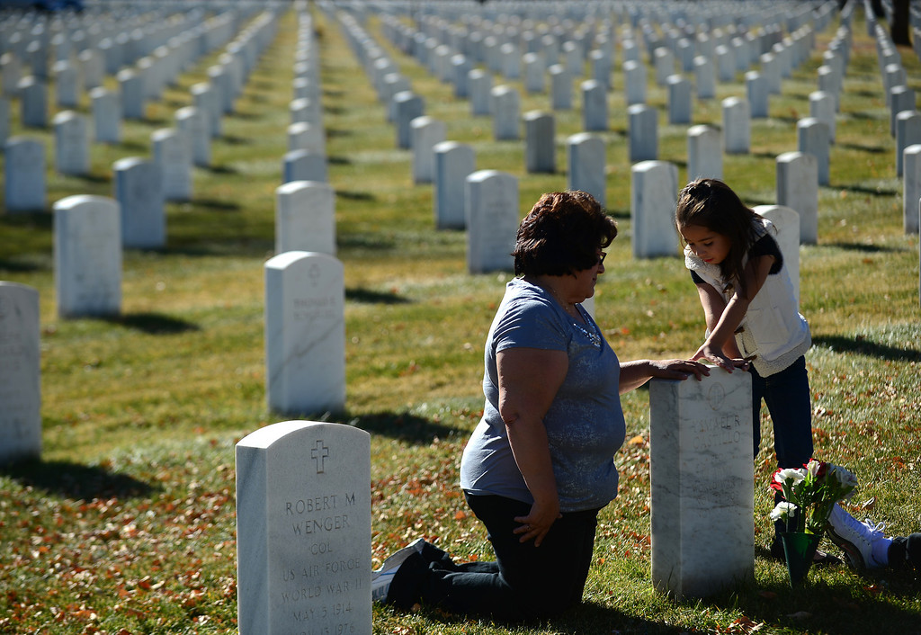 . Angela Barba, left and her niece Jaylin Minter, 6, touch the grave of Barba\'s father Ysmael Castillo after the 36th annual Remembrance ceremony of Veteran\'s Day at Fort Logan Cemetery in Lakewood, CO  on November 11, 2013. Castillo was a in the Army and was a WWII vet who died in 1976.  The family comes many times through out the year to visit the grave.    (Photo By Helen H. Richardson/ The Denver Post)