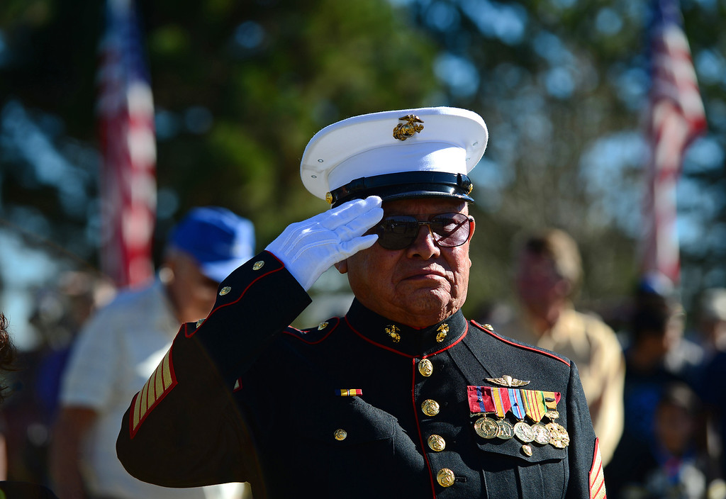 """. LAKEWOOD, CO - NOVEMBER 11, 2013: Pedro Galan, a former gunnery sergeant with the Marines and who fought in Vietnam and Korea, salutes during the singing of God Bless America at the 36th annual Remembrance ceremony of Veteran\'s Day at Fort Logan Cemetery in Lakewood, CO  on November 11, 2013. The day was marked with a 21 gun rifle salute, \""""Echo taps\"""" played by buglers and the release of white birds of freedom.  The benediction was given by Jackie Newlander.  (Photo By Helen H. Richardson/ The Denver Post)"""