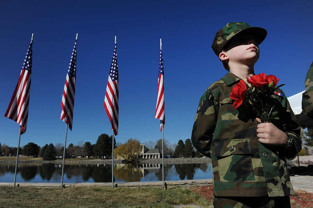 ". LAKEWOOD, CO - NOVEMBER 11, 2013: Matthew Krneta, with the Mountain View Young Marines, holds flowers for  the 36th annual Remembrance ceremony of Veteran\'s Day at Fort Logan Cemetery in Lakewood, CO  on November 11, 2013. The day was marked with a 21 gun rifle salute, ""Echo taps\"" played by buglers and the release of white birds of freedom.  The benediction was given by Jackie Newlander.  (Photo By Helen H. Richardson/ The Denver Post)"