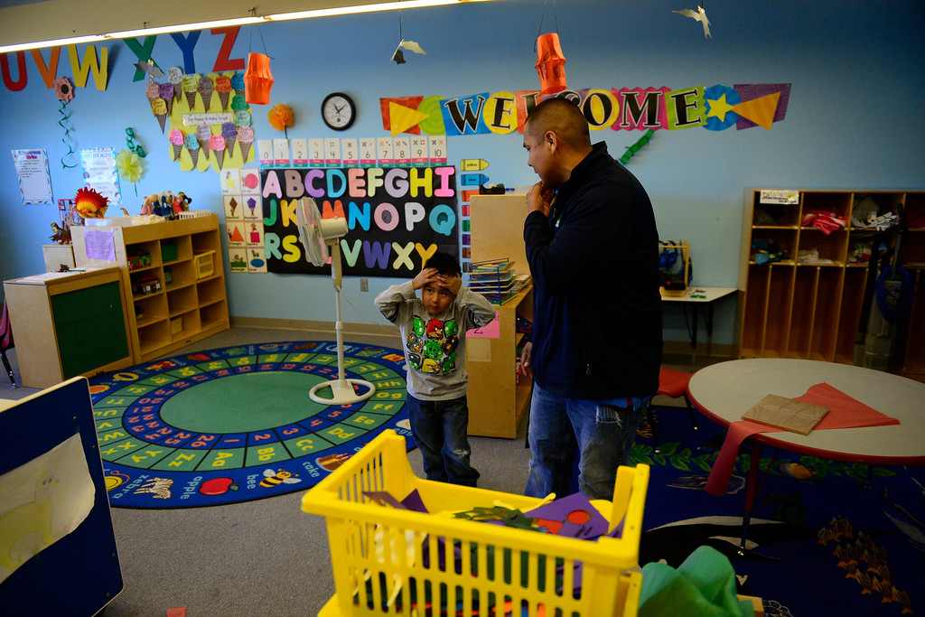 . Ah\'Dae Lang holds his head in hopes of being able to leave his Head Start classroom with his parents, Cedric Lang (pictured) and Sherrell Williams, as the couple gives a tour of the Ute Mountain Ute reservation from a visiting group from San Juan College in Farmington, New Mexico. The elder Lang said he hopes that his people can begin moving forward starting with the youth. (Photo by AAron Ontiveroz/The Denver Post)