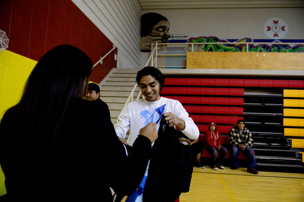 . Gabe Richards gives his jacket to his wife, Fernessa Dutchie-Richards, before playing in a men\'s league basketball matchup at the community recreation center. Basketball is almost a way of life on the reservation as many youths grow up playing the sport. Despite the high level of interest, few leave the reservation to play beyond high school despite a high level of talented players. (Photo by AAron Ontiveroz/The Denver Post)