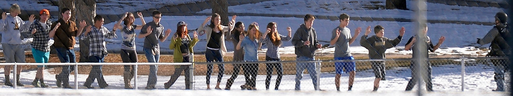 . CENTENNIAL, CO - Students with their arms up are escorted to the football field after being evacuated fro the school. At a about 12:30 pm a student was spotted inside Arapahoe High School carrying a shotgun December 13, 2013. The gunman was targeting a teacher at the school. The gunman shot two students in the process and then turned the gun on himself. DECEMBER 13:  (The Denver Post)