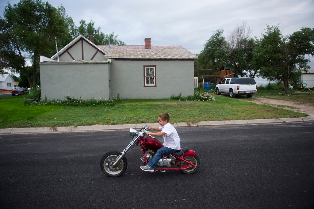 . CHEYENNE WELLS, CO - AUGUST 08, 2013: Ethen Garay, 6, rides his motorcycle past his home on a Thursday evening. The Garay\'s bought the home for $7000 and fixed it up where they now live with two kids and frequent visitors. (Photo By Grant Hindsley/The Denver Post)