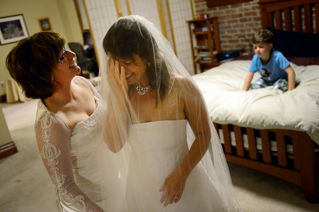 . DENVER, CO. - APRIL 29: Fran, left, and Anna Simon try on their wedding dresses while their son Jeremy, 5, watches from the bed at their home in Denver, CO April 29, 2013. The couple hope to be one of the first in Colorado to be joined in Civil Union just after midnight on May 01, 2013 when the Civil Union Act takes effect. The couple has been together 10 years and wore the same dresses in 2005 when they had a wedding ceremony at the Denver Botanical Gardens. (Photo By Craig F. Walker/The Denver Post)