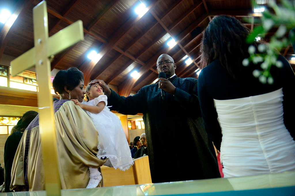 . DENVER, CO - NOVEMBER 24: Pastor Victor lane performs a blessing on Tatyianna Skyy Parrish during the Sunday service. Lane will be installed as the church\'s pastor in December. Macedonia Baptist church. (Photo by AAron Ontiveroz/The Denver Post)