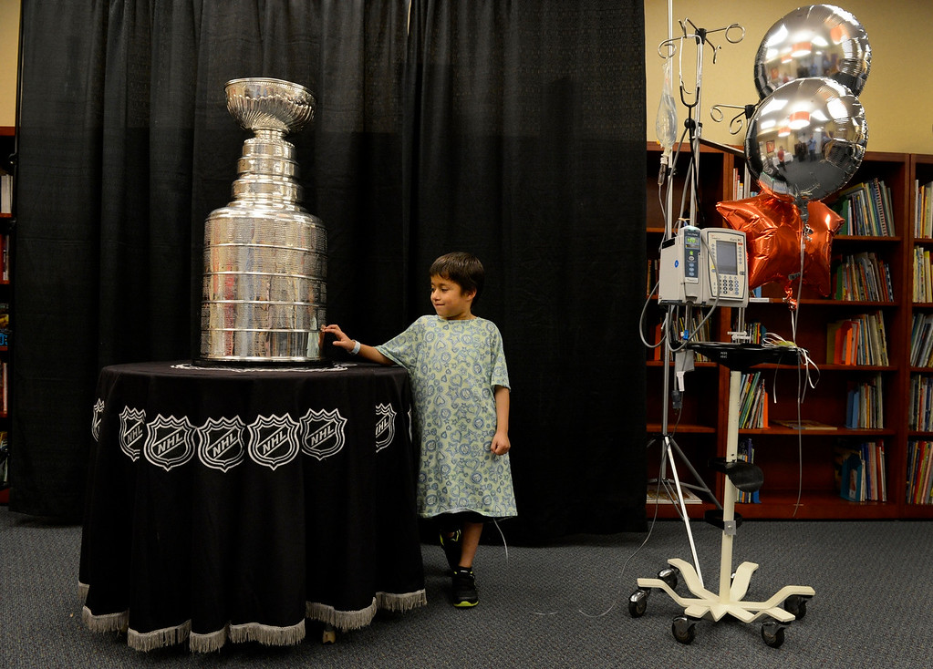 . DENVER, CO. - MAY 15: Miguel Calihua-Gonzales, 6, gets up close and personal with the Stanley Cup at Rocky Mountain Hospital for Children in Denver, CO May 15, 2013. Miguel, of Minatare, NE, is a patient at the hospital being treated for Hodgkin\'s lymphoma. The hospital, Make-A-Wish, Discover and the National Hockey League teamed up to grant the wish of Logan Piz, 13, to spend a day with the Stanley Cup and share it with friends, family and supporters. Logan has not played hockey since he was diagnosed with Ewing��ôs sarcoma in November 2012. (Photo By Craig F. Walker/The Denver Post)