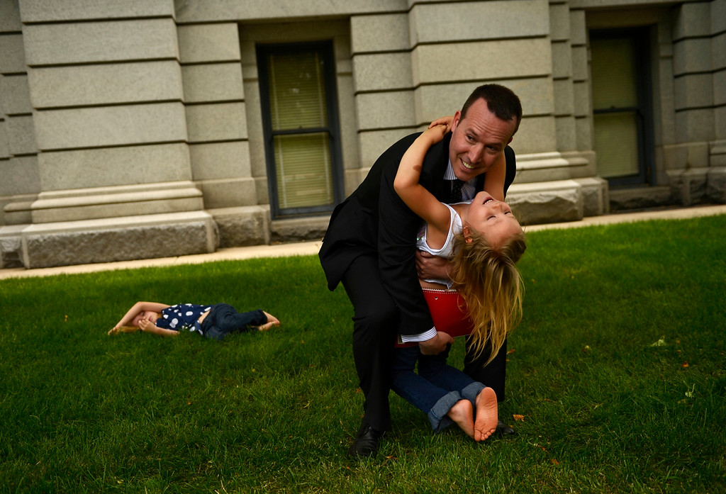 . DENVER, CO-June 24, 2013: Six-year-old Coy Mathis hugs her attorney Michael Silverman outside the Colorado State Capitol after announcing that the Colorado Civil Rights Division has ruled in favor of Coy Mathis, whose school had barred her from using the girls� bathroom at her elementary school because she is transgender, June 24, 2013. Coy was labeled male at birth, but has always known that she is a girl, which she has expressed since she was 18 months old. Coy\'s older sister, Dakota, 9, lies in the grass behind them. (Photo By RJ Sangosti/The Denver Post)
