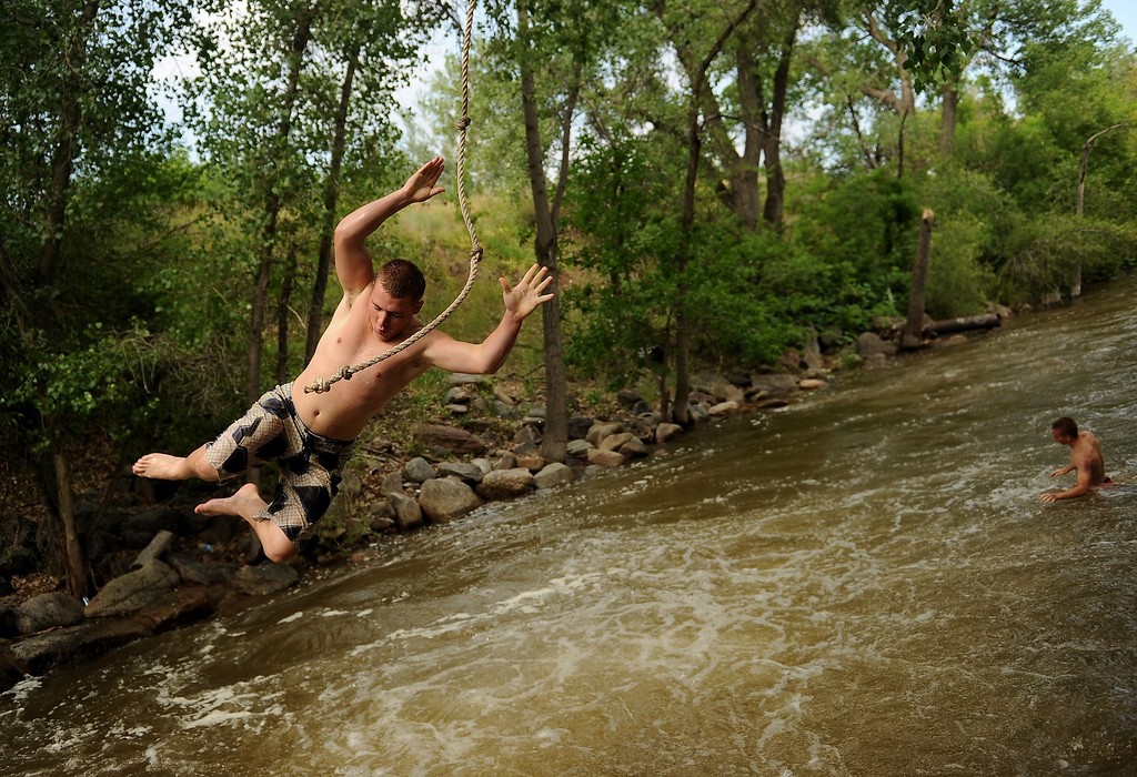 . BOULDER, CO - JULY 15:   Blake Carver, 18, of Thornton, gets ready to fly into Boulder Creek off of the popular rope swing near Eben G. Fine park in Boulder, CO on July 15, 2013.  With three consecutive days of rain creeks, rivers and reservoirs are swollen with water. Photo by Helen H. Richardson/The Denver Post)