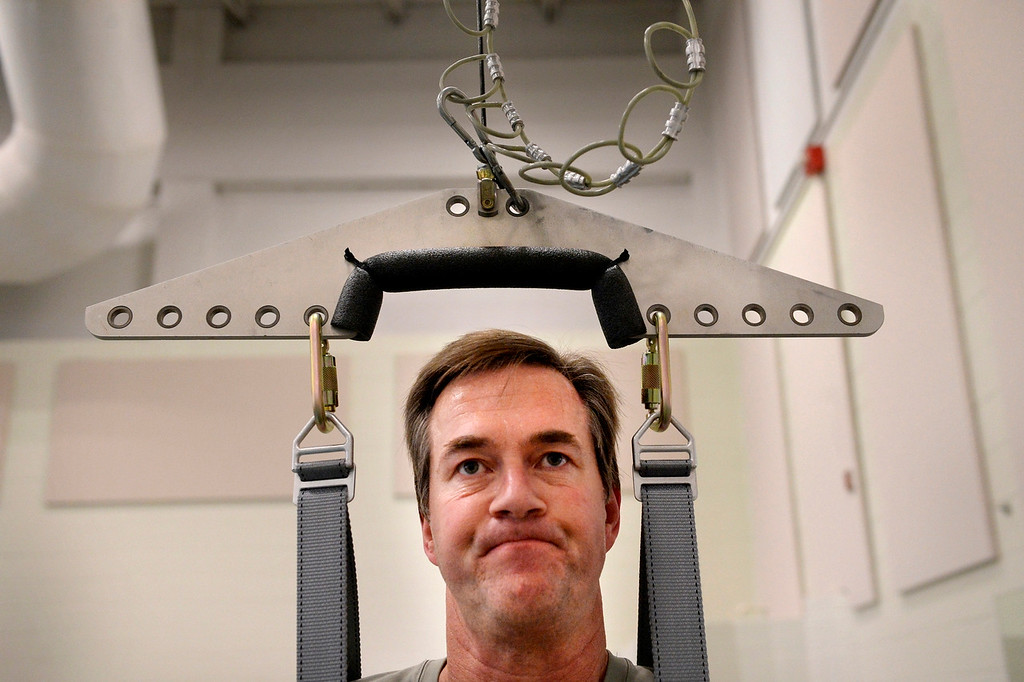 ". ENGLEWOOD, CO. - AUGUST 21: Suspended in a harness Kyle Pearson works out on the TheraStride at Craig Hospital in Englewood, CO August 21, 2013. He remembers that earlier in his recovery, ""I called that machine my nemesis. I\'d take two steps and trip, take two steps and trip... I won\'t say that I\'m friends with the treadmill, but we\'re not archenemies anymore.\""  (Photo By Craig F. Walker / The Denver Post)"