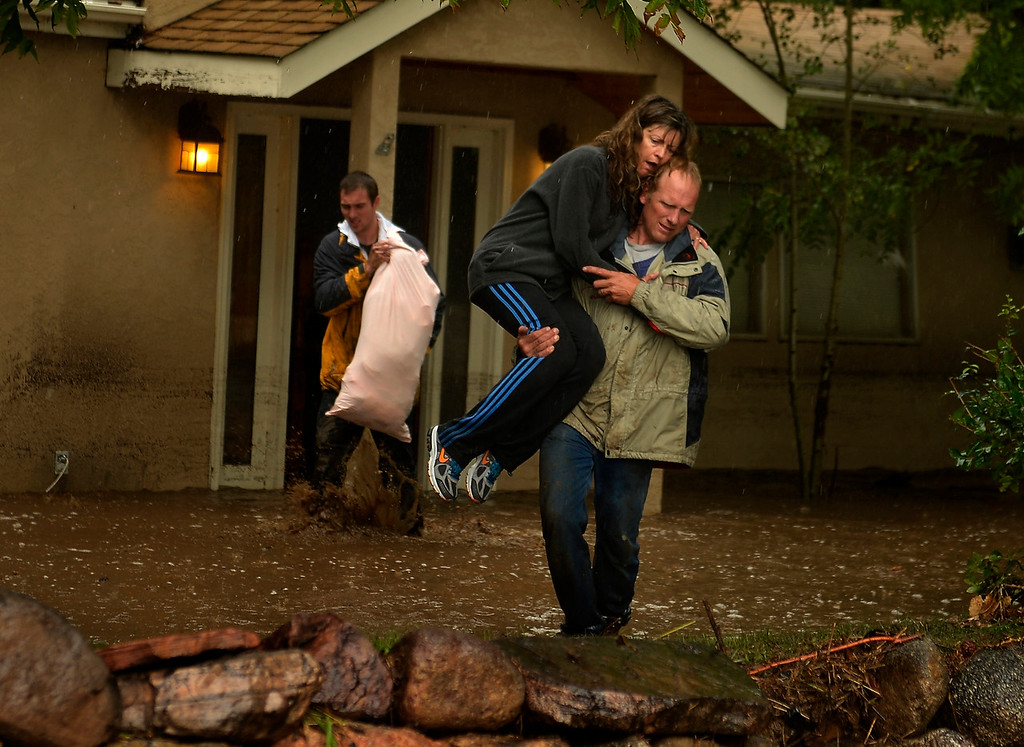 . BOULDER, CO. - September 12: Kyle Schuler trudges through the water and mud as Cheryl Schuler is carried from her home by her husband Kim after being at their home on Upland Ave to salvage what they can when heavy overnight rains flooded 4 Mile Creek in Boulder September 12, 2013 Boulder, Colorado. (Photo By Joe Amon/The Denver Post)