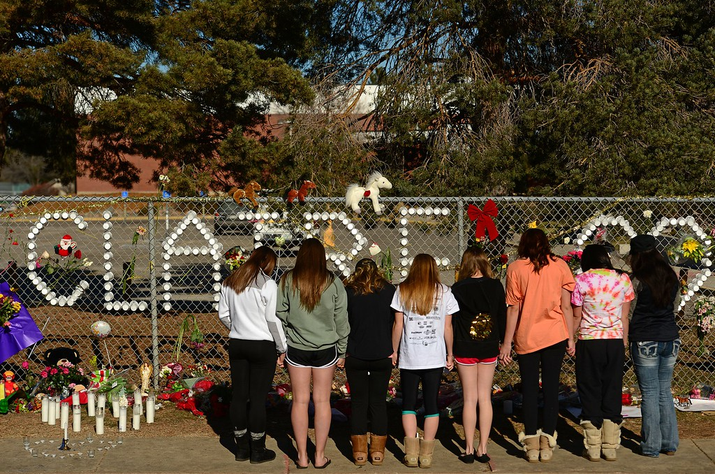 . CENTENNIAL, CO - DECEMBER 17, 2013: Members of the Arapahoe High School cheerleading squad came to leaves notes, flowers and  their prayers for shooting victim Claire Davis at a tribute for her on a fence outside the school along Dry Creek road  in Centennial, CO on December 17, 2013. Davis remains in critical but stable condition in a coma at Littleton Adventist Hospital.  (Photo By Helen H. Richardson/ The Denver Post)