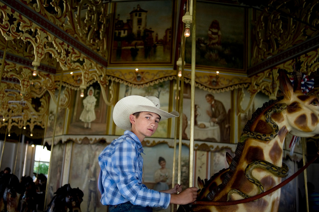 . BURLINGTON, CO - AUGUST 09, 2013: Jace Roselle, 13, rides a snake-wrapped giraffe on the Kit Carson County Carousel during a break between competitions at the neighboring rodeo in Burlington, Co. (Photo By Grant Hindsley/The Denver Post)
