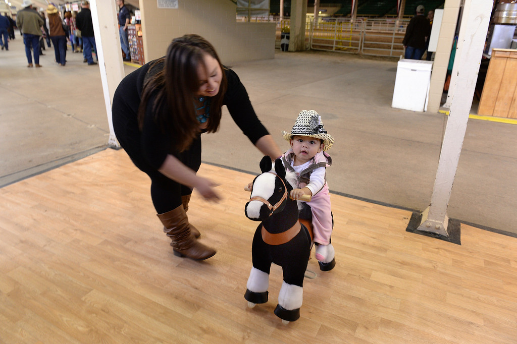 . DENVER, CO. - JANUARY 15: Allie MacCary, age 10-months, got an assist from Mackenzie Wilusz, left, on her Pony Pal ride inside the stadium on the National Western Stock Show grounds Wednesday afternoon, January 15, 2014. The stuffed toys have wheels to scoot across the floor. Photo By Karl Gehring/The Denver Post