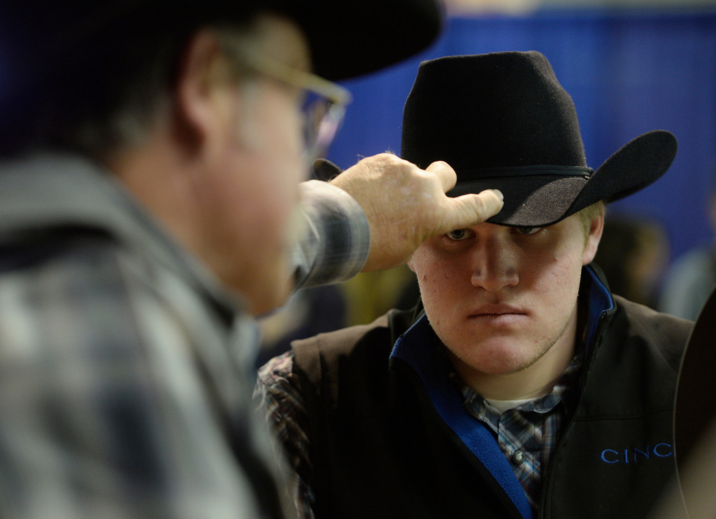 . DENVER, CO. - JANUARY 11:  Nick Fintelmann, 16, right, from Loveland Colorado, gets his cowboy hat back from Rick Bishop, left, who just steamed and cleaned Fintelmann\'s hat on opening day of the National Western Stock Show Saturday, January 10, 2014. (Photo By Andy Cross / The Denver Post)