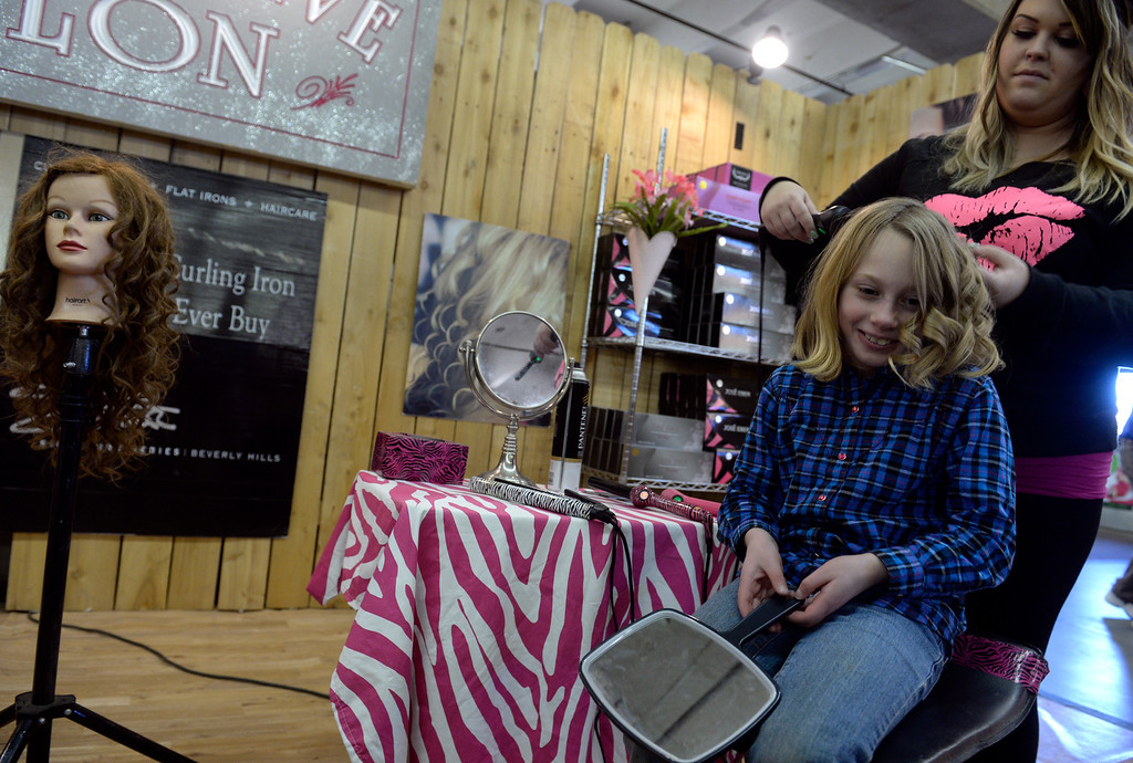 . DENVER, CO - JANUARY 21: Cheyenne Leigh, right, shows Sullivan Morrison, 8, of Nederland the special curls that can be made with the José Eber curling wand. Leigh travels to different events around the country selling products for Webster Enterprises. Vendors work to sell their wares on the free day at the National Western Stock Show on Tuesday, Jan. 21, 2014. Many of the vendors said shopping traffic was down a bit on Sunday due to the Denver Broncos playoff game but the Monday Dr. Martin Luther King, Jr. holiday brought large crowds. (Photo by Kathryn Scott Osler/The Denver Post)