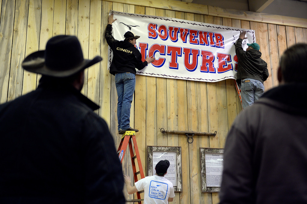 . DENVER, CO. - JANUARY 10: Cole Hopkins and Zilla Lapp used ladders to hang a banner above a booth that will offer souvenir photographs of guest atop live animals at the stock show. The National Western Stock Show starts Saturday, January 11, 2014. Photo By Karl Gehring/The Denver Post