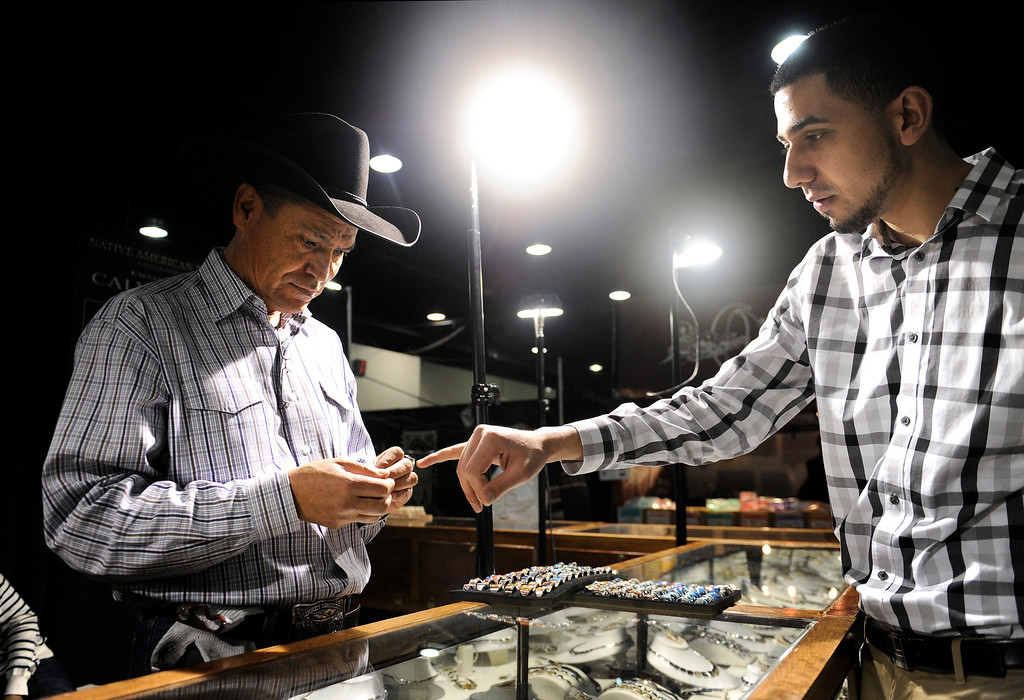 . Jewelry artist Calvin Begay, left, looks at some of his artwork with assistant Hamed Sarameh during the Colorado Indian Market on Jan. 19 at the Denver Mart in Denver, Colo. Photo by Jamie Cotten, Special to The Denver Post