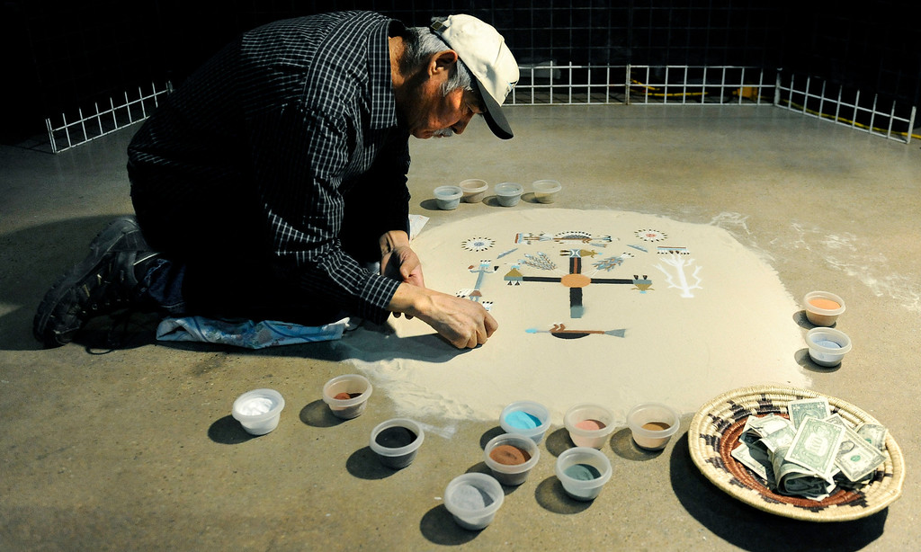 . Artist Wallace Ben creates a piece of sand art on Jan. 19 during the Colorado Indian Market at the Denver Mart in Denver, Colo. Ben said all the sands he uses are naturally colored and not dyed. Photo by Jamie Cotten, Special to The Denver Post