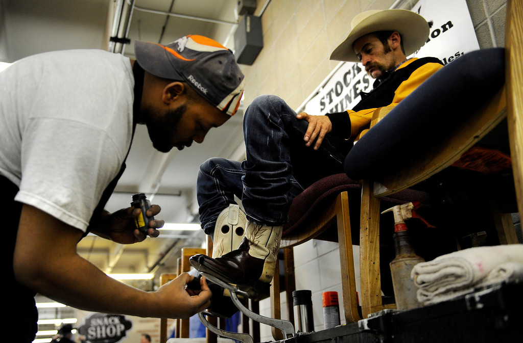 . Kalum Harris, left, shines shoes for customer Brent Bond on Jan. 19 at the National Western Stock Show the Denver Coliseum. Photo by Jamie Cotten, Special to The Denver Post