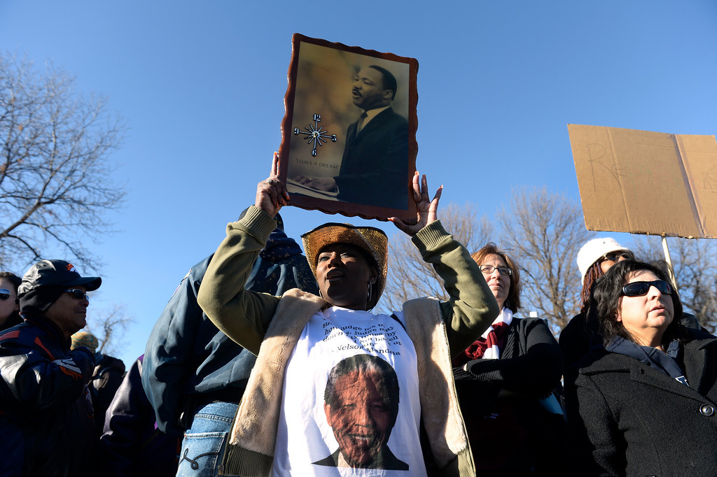 . Bridget Johnson of Denver joins other participants in the 29th annual Martin Luther King, Jr. Marade as they gather at the King memorial site in City Park in Denver to listen to speeches and songs honoring King. Then the crowd makes its way marching down E. Colfax Ave. to Civic Center Park where birthday cake is served to all. (Photo by Kathryn Scott Osler/The Denver Post)