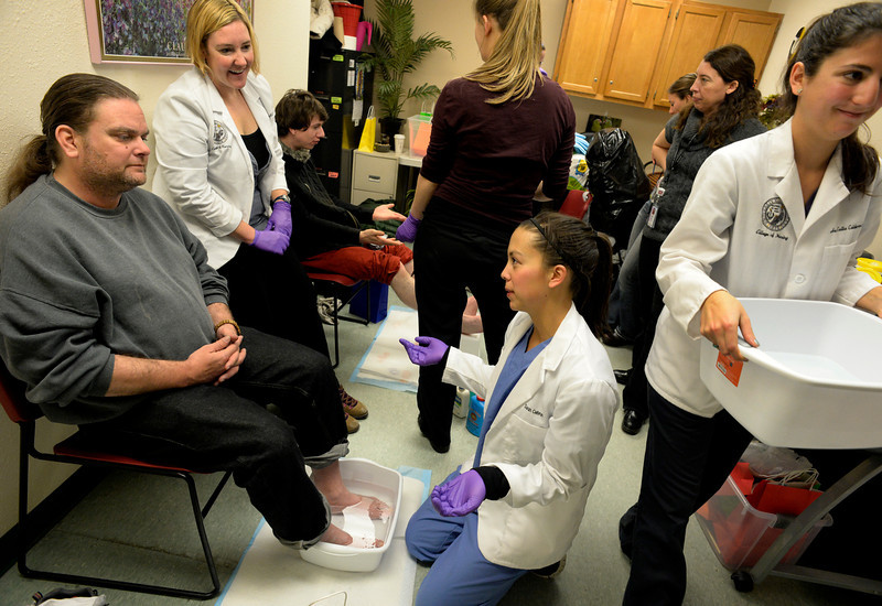 . Medical student Sarah Cebron, center, talks about foot care with Mike Flynn during the CU UNITE Foot Care Clinic at the St. Francis Center in Denver, CO March 01, 2014. (Photo By Craig F. Walker / The Denver Post)