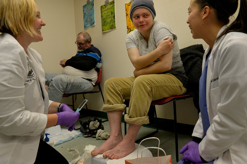 . Jennifer Sauceda, center, is treated by nurse practitioner student, Ashley Shurley, left, and medical student Sarah Cebron during the CU UNITE Foot Care Clinic at the St. Francis Center in Denver, CO March 01, 2014.  (Photo By Craig F. Walker / The Denver Post)