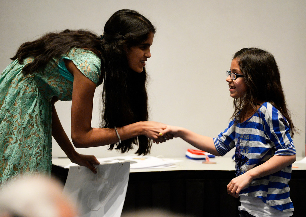 . DENVER, CO. - MARCH 08: 2013 winner of the Colorado State Spelling Bee, Himanvi Kopuri,  left, greets 2014 contestant, Cheyenne Trujillo, a third-grader from Hackberry Hill Middle School, after Trujillo was misspelled a word at the 74TH Annual Colorado State Spelling Bee Saturday, March 08, 2014 at the Colorado Convention Center. (Photo By Andy Cross / The Denver Post)