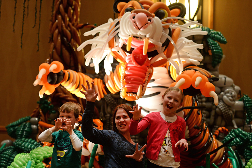 . Kristina Mordecai, middle, poses with her kids Riley, 8, right and Ryder, 4, left for a photo for their friend in front of the balloon design entitled A Mothers Love, at the International World Balloon Convention in Denver, Co on March 30, 2014.   A Mother\'s Love, created by balloon artist Dennis Scott took him and 21 other artists 27 hours and 15,000 balloons to complete.  Balloon artists from around the world competed in a variety of categories of balloon design.   Photo By Helen H. Richardson/ The Denver Post)