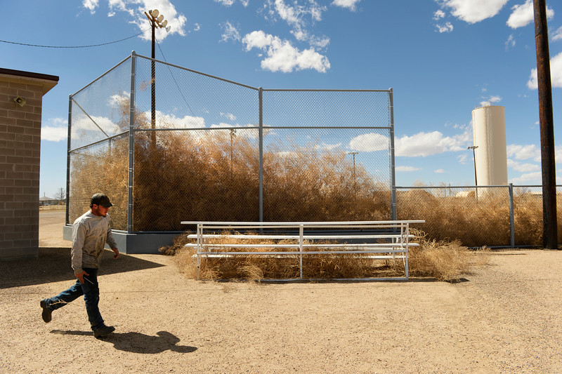 . EADS, CO - MARCH 31: A.J. Bolin, who is working on the sprinkler system at the Eads baseball field, hurries to turn off a water valve, Monday, March 31, 2014. High winds have blown thousands of tumbleweeds up against the backstop of the ball park.  (Photo by RJ Sangosti/The Denver Post)