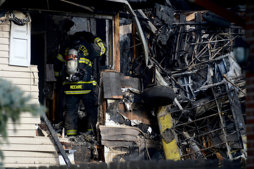 . A North Metro fireman works in the scene of the crash. A plane crashed into a home in Northglenn 110th Avenue and Livingston on May 5, 2014. (Photo by AAron Ontiveroz/The Denver Post)