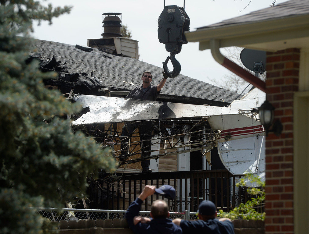 . NORTHGLENN, CO. - MAY 06: A worker grabs the hook from a crane  Tuesday morning, May 06, 2014 to hook up to straps wrapped around the wreckage of an aircraft that crashed into the back of a house at 11006 Livingston Dr. in Northglenn the day before, May 05, 2014. Northglenn firefighters, below, keep a close eye on the lift. The pilot walked away from the crash uninjured, nobody was at the home at the time of the crash. (Photo By Andy Cross / The Denver Post)