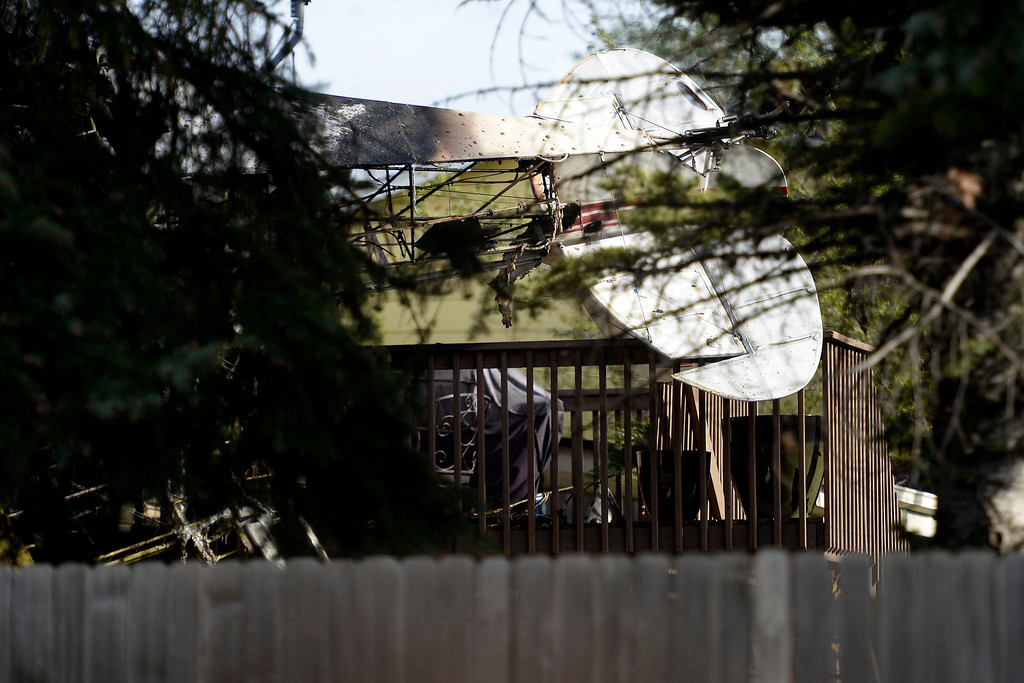 . The back of a small plane can be seen peeking out from behind a home. A plane crashed into a home in Northglenn 110th Avenue and Livingston on May 5, 2014. (Photo by AAron Ontiveroz/The Denver Post)