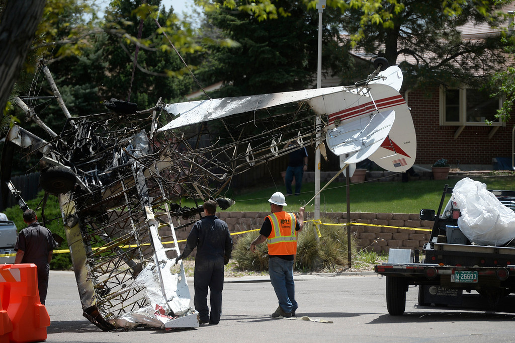 . NORTHGLENN, CO. - MAY 06: Crews guide the wreckage of an aircraft that was pulled out of the back of a home Tuesday morning, May 06, 2014 to the street, next to a flat-bed trailer.  The airplane crashed into the back of the home at 11006 Livingston Dr. in Northglenn the day before, May 05, 2014. (Photo By Andy Cross / The Denver Post)