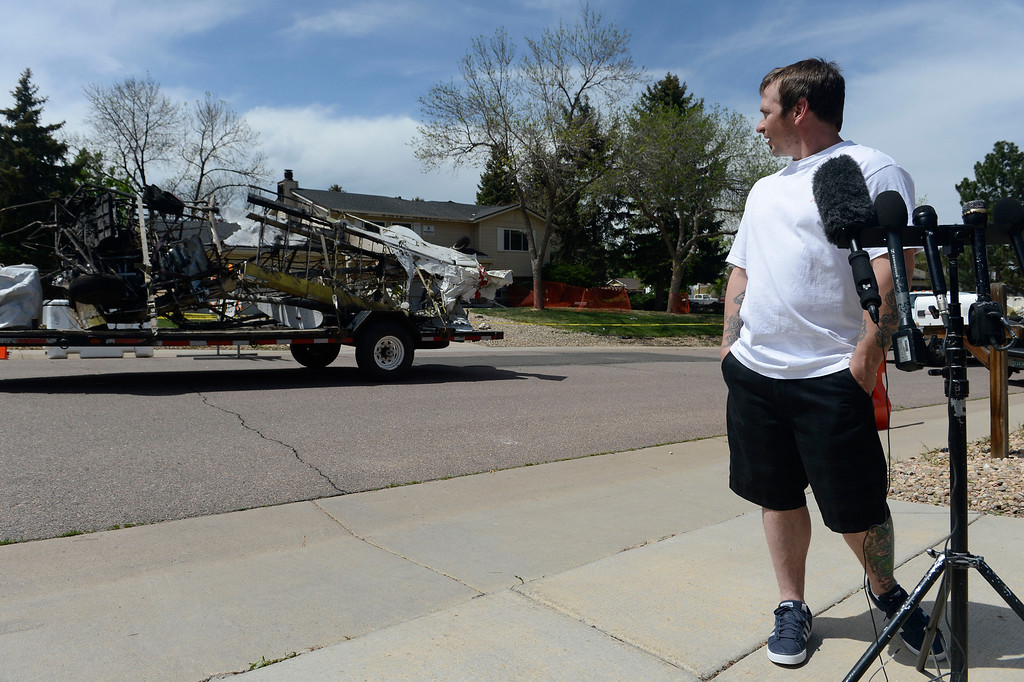 . NORTHGLENN, CO. - MAY 06: A truck pulling a flat-bed trailer, loaded with a carcass of a small plane, drives past homeowner, Matthew Richardson, while he was talking to the press across the street from his heavily damaged home Tuesday, May 06, 2014. On Monday, the plane crashed into the back of his house at 11006 Livingston Dr. in Northglenn, the pilot walked away uninjured, Richardson and family were not home at the time of the crash.  (Photo By Andy Cross / The Denver Post)