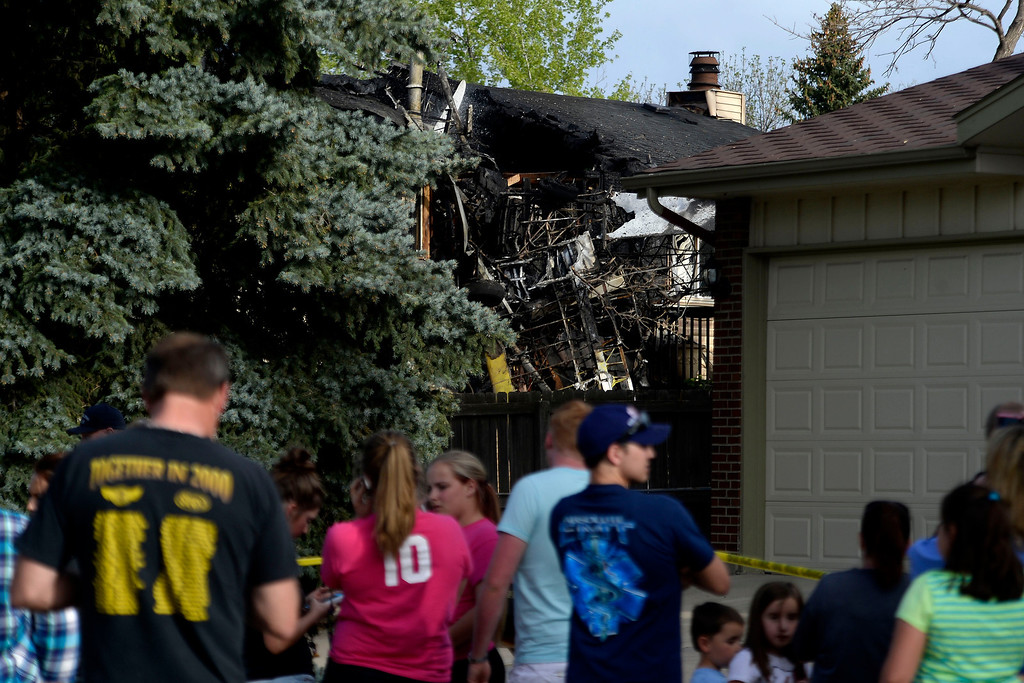 . People look on from behind the police tape at the scene of the crash. A plane crashed into a home in Northglenn 110th Avenue and Livingston on May 5, 2014. (Photo by AAron Ontiveroz/The Denver Post)